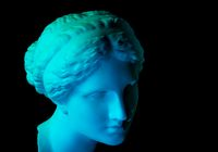 Gypsum copy of ancient statue Venus head isolated on a black background. Plaster sculpture woman face. Blue toned.