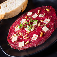 Carpaccio of beef with pine nuts, colorful pepper and Parmesan cheese