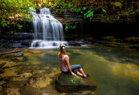 Woman at waterfall and swimming hole in bushland wilderness