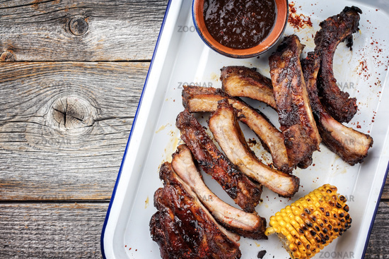 Barbecue spare ribs St Louis cut with hot honey chili marinade as top view in a skillet with copy space left