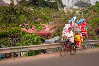 Elderly man transports his inflatable children toys via bicycle, Laos.