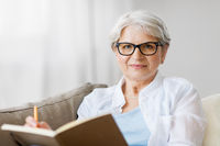 senior woman writing to notebook or diary at home