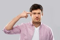 bored man making headshot by finger gun gesture