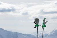 Gloves on ski poles and snowy winter mountains in background
