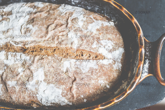 Bake bread - the finished bread, dusted with flour, fresh and crispy.