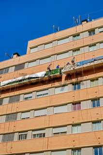 workers on the exterior scaffold elevator to repair the building