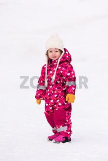 little girl having fun at snowy winter day