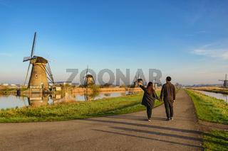 Rotterdam Netherlands, Love couple walking with Dutch Windmill at Kinderdijk Village
