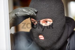 Einbrecher mit Sturmhaube späht durch Fenster