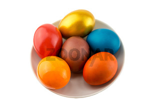 Six bright orange eggs and gold lie on a ceramic saucer on a white isolated background