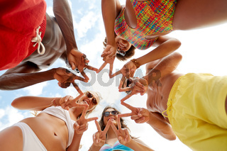 happy friends showing peace in circle on beach