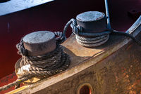 Two rusty mooring bitts and rope