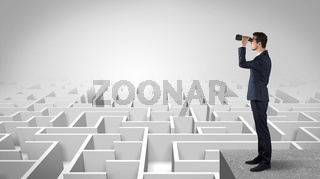 Man standing on top of a maze with binoculars