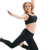 Slim sportswoman gracefully jumping in studio
