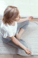 A Woman Over the Age of 50 is Doing Yoga at Home.