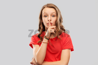 teenage girl in red t-shirt with finger on lips