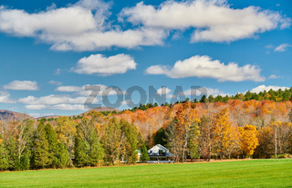 Autumn landscape with house in forest