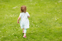 happy little baby girl running at park in summer