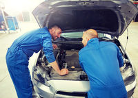 mechanic men with wrench repairing car at workshop