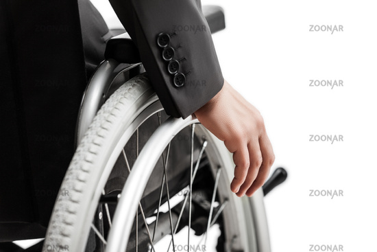 Invalid or disabled businessman in black suit sitting wheelchair
