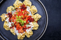 Traditional Turk manti steamed with mincemeat and paprika tomato salad as top view on a plate with copy space right