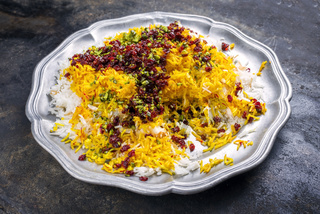 Traditional Iranian steamed saffron rice with berberis and pistachios as closeup on a pewter plate