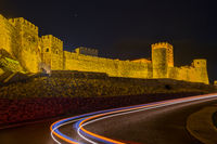 Illuminated walls and towers of Rabati Castle and traces of car headlights on the road