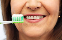 senior woman with toothbrush brushing her teeth