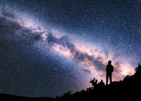 Woman with backpack on the hill against colorful Milky Way