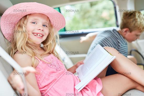 Glückliches Mädchen im Auto mit einem Buch