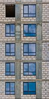 Vertical Row of the windows of apartment building in development state with reflections of blue sky in window glass