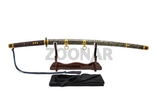 'Kai Gunto' : Japanese Marine Sword From World War 2 with scabbard wrapped by ray skin on wooden stand and  bag in front of, isolated in white background.