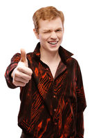 red-haired young man close-up in a red shirt raises his thumb up and smiling, isolated on white background