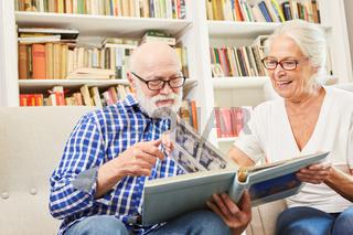 Senioren Paar mit Demenz betrachtet alte Fotos