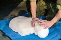 adult education practitcing CPR chest compressioon on a dummy.