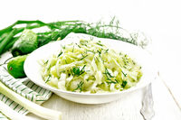 Salad of cabbage with cucumber in plate on light board
