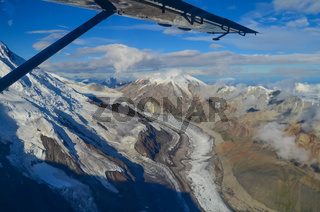 Aerial view of Alaska mountaion range around Denali peak from a plane with glaciers around and blue sky above. Denali National Park and Preserve, Alaska, United States