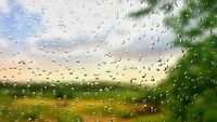 A view of the landscape through a wet window with digitally added of rain drops.