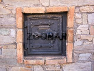 Tür von einem alten Backofen außen an der Fassade