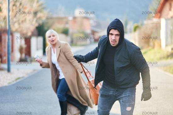 Dieb beim Stehlen einer Handtasche von Frau