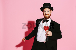 Smiling and dancing man in a tuxedo and top hat holding a red heart