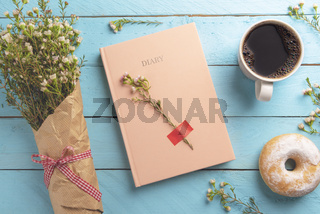 Diary notebook and delicious breakfast on a wooden table.