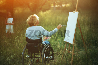 Woman in wheelchair drawing on easel outside