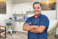 Hispanic Male Doctor Standing In Office