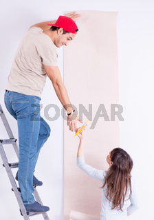 The young family doing renovation at home with new wallpaper