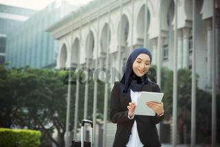 Muslim woman working on table pc outdoor