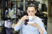 Beautiful cheerful female client drinking a cup of coffee in beauty salon