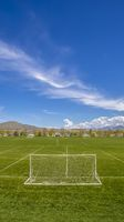 Panorama Soccer field with scenic view of towering mountain and vibrant blue sky