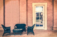 waiting room outside modern elegant with table magazines wooden armchairs stone walls and white door