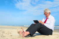 Business man upset working on tablet at the beach